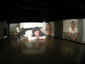installation view of 5-channel video projected on the walls and large floating walls in an art gallery