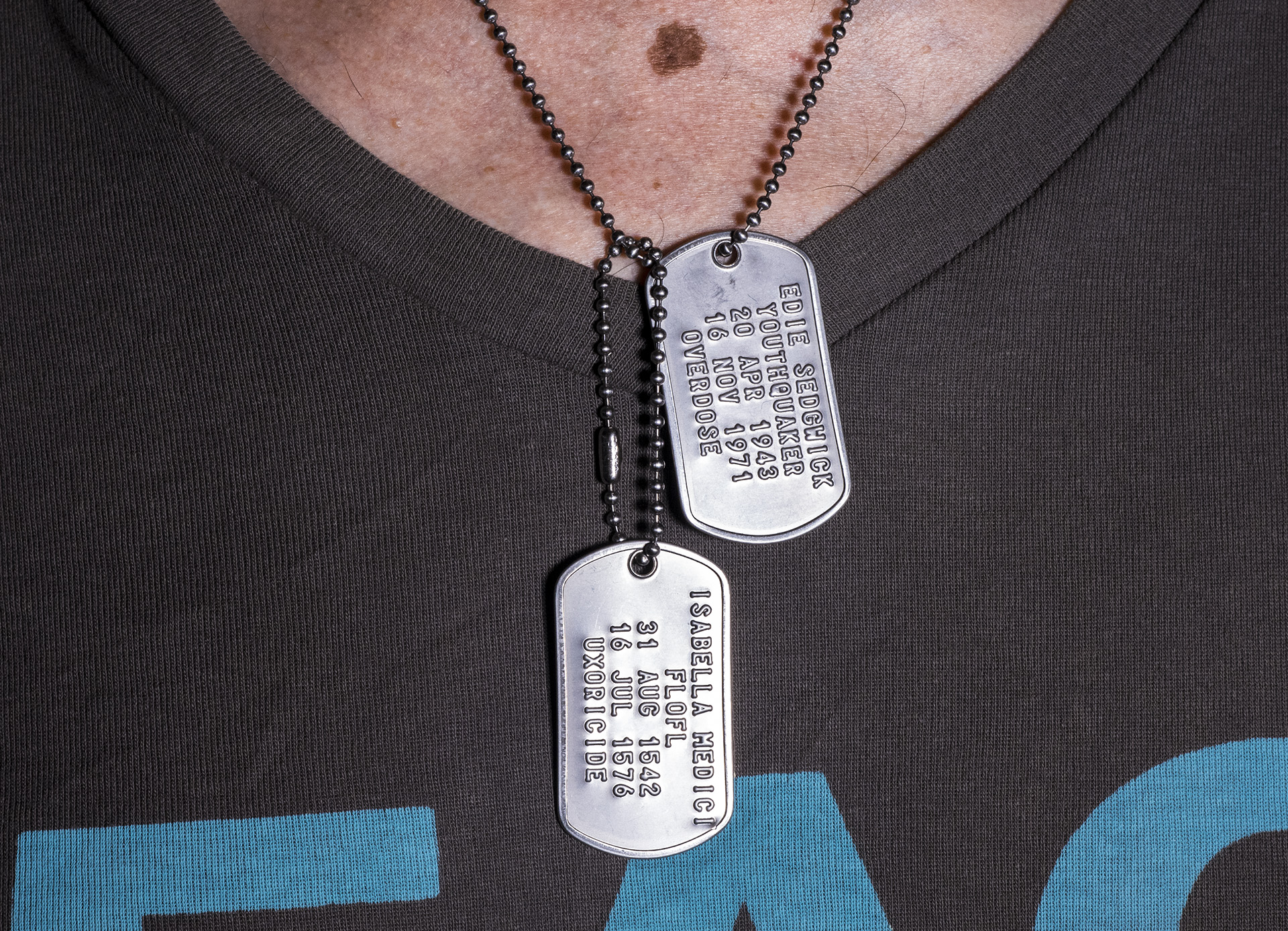"""photo of a pair of dog tags around a neck and over a v-neck t-shirt. 1st tag reads: """"Isabella Medici, FLOFL, 31 Aug 1542, 16 Jul 1576, uxoricide"""". 2nd tag reads: """"Edie Sedgwick, Youthquaker, 20 Apr 1943, 16 Nov 1971, overdose""""."""