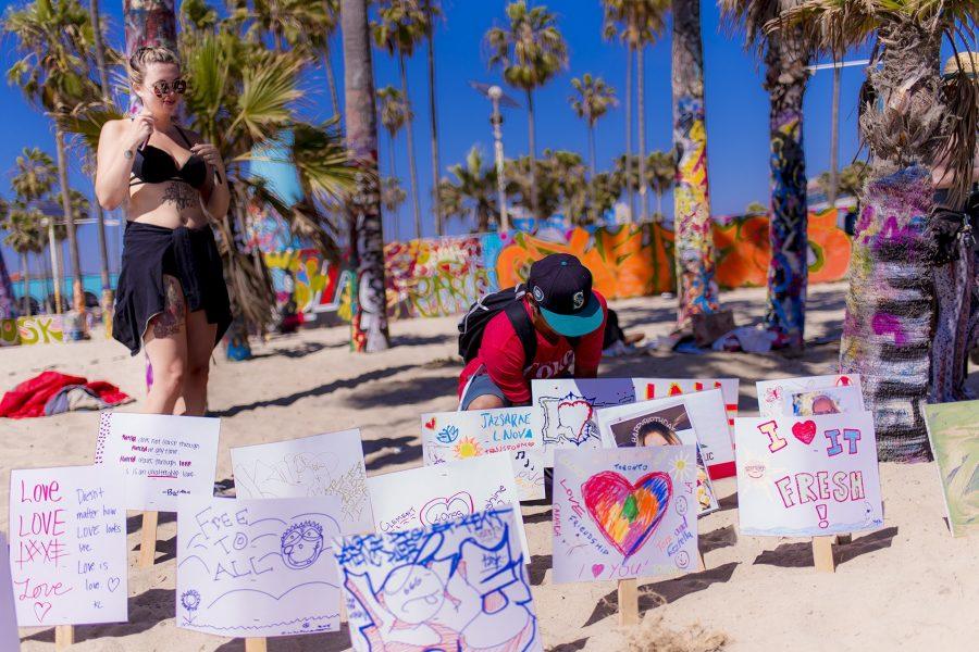 """visitors making """"Love Signs"""" at Love Beach at Venice Beach, CA"""