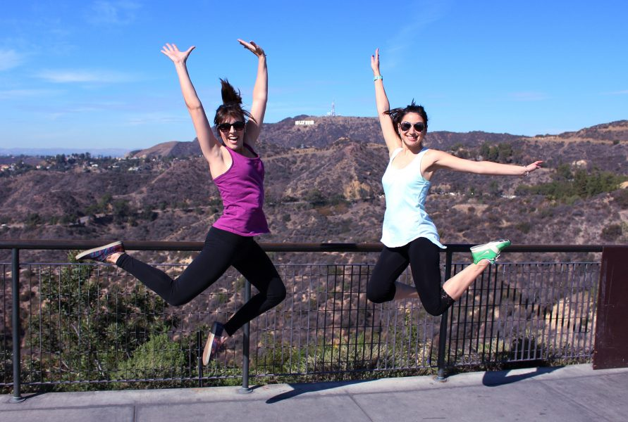 Kamal & Rebecca at Griffith Observatory jumping in the air with the Hollywood Sign behind them.