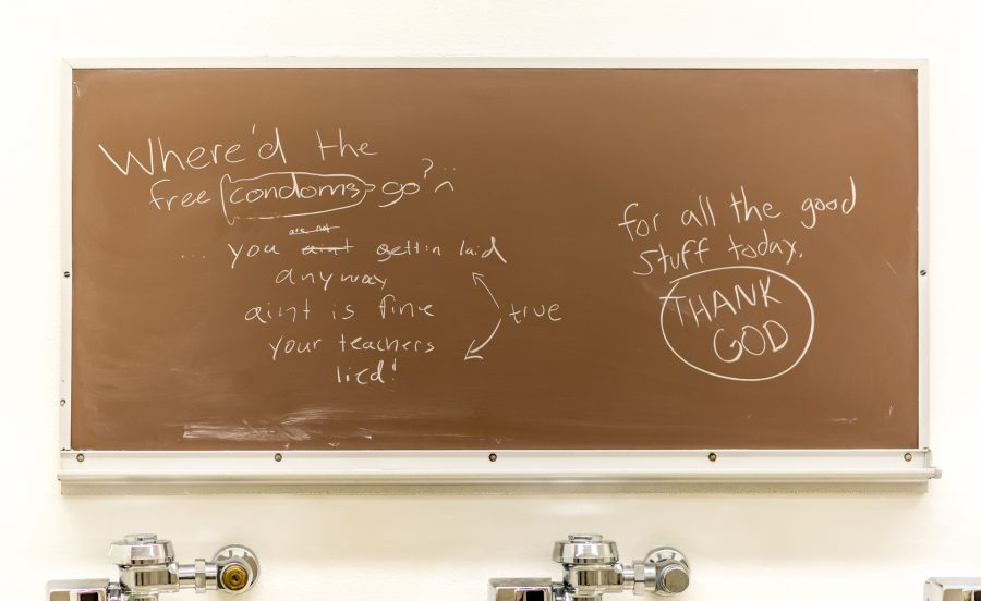 brown chalkboard in the men's room with various markings in white chalk