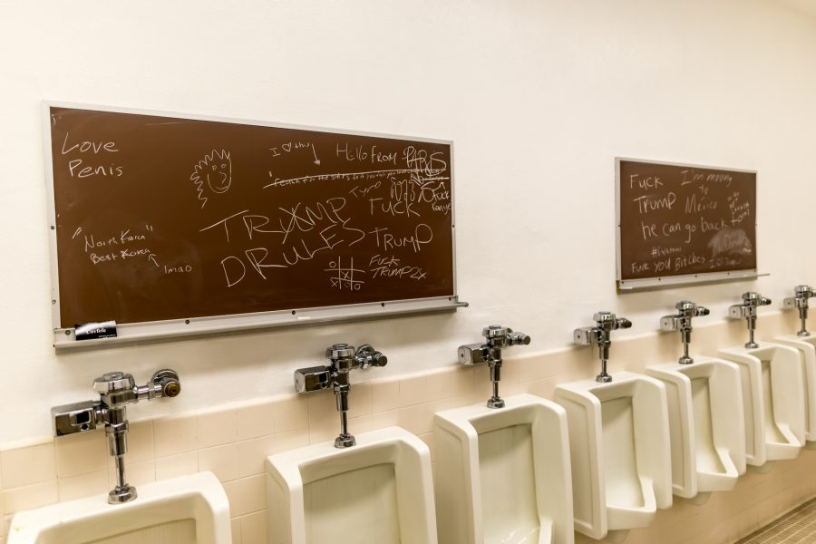 photo of 2 chalkboards mounted over a row of urinals