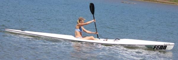 photo of a woman in a bikini paddling a Fenn Bluefin surf ski on flat water