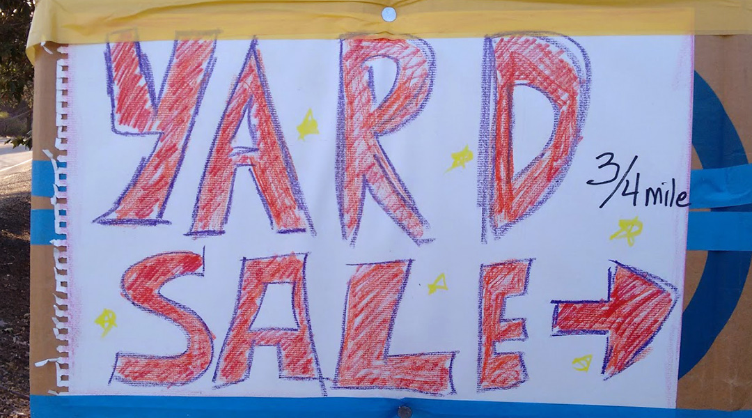 "Sign with hand lettering ""Yard Sale"" and an arrow with the marking 3/4 mile"