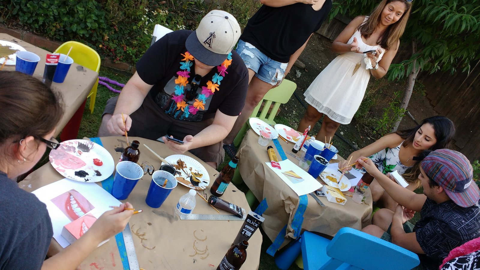 people painting at a backyard party