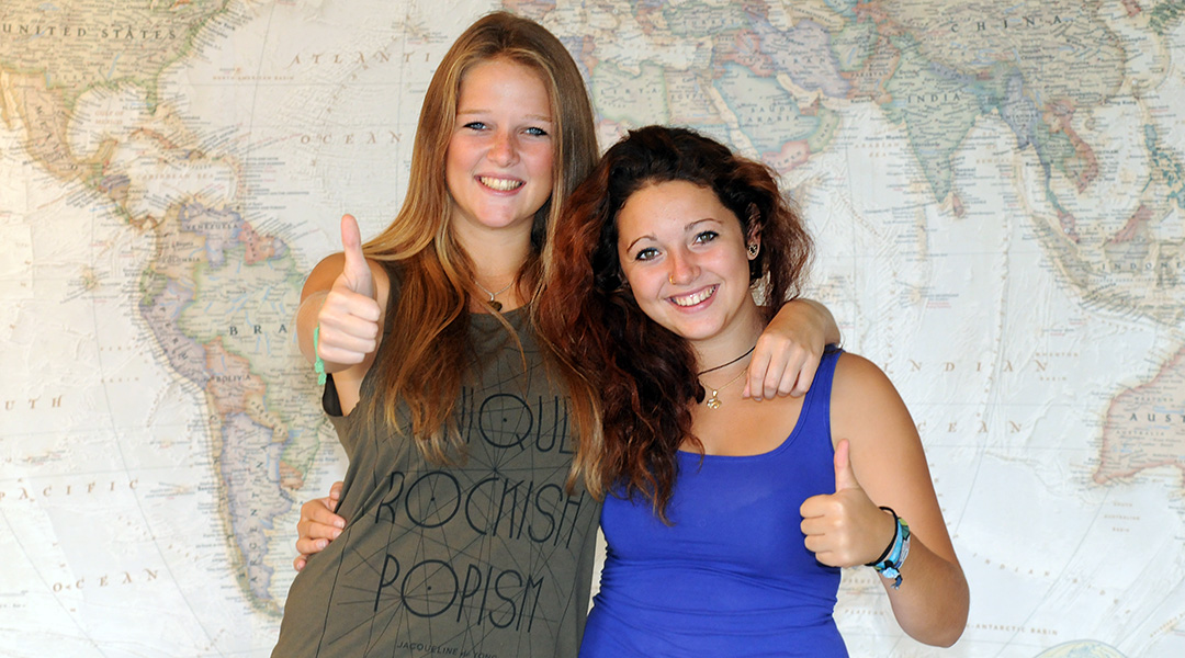 two women standing in front of a world map