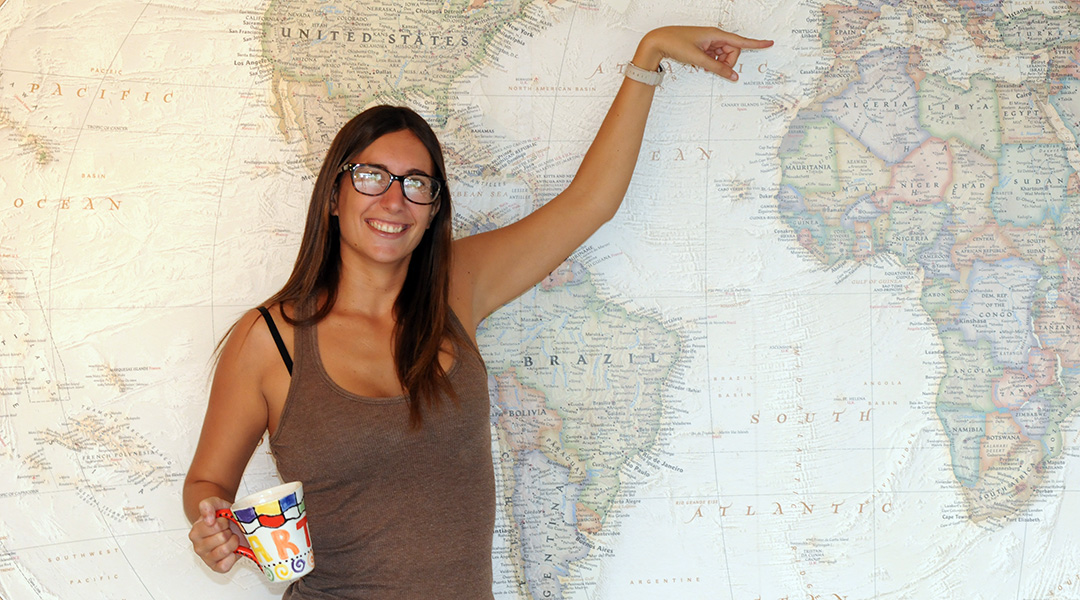 Larra Royo standing in front of a map of the world and pointing to Spain