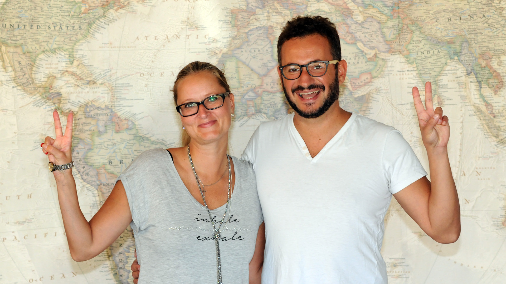 Two people standing in front of a ten foot wide map of the world, smiling and making peace signs