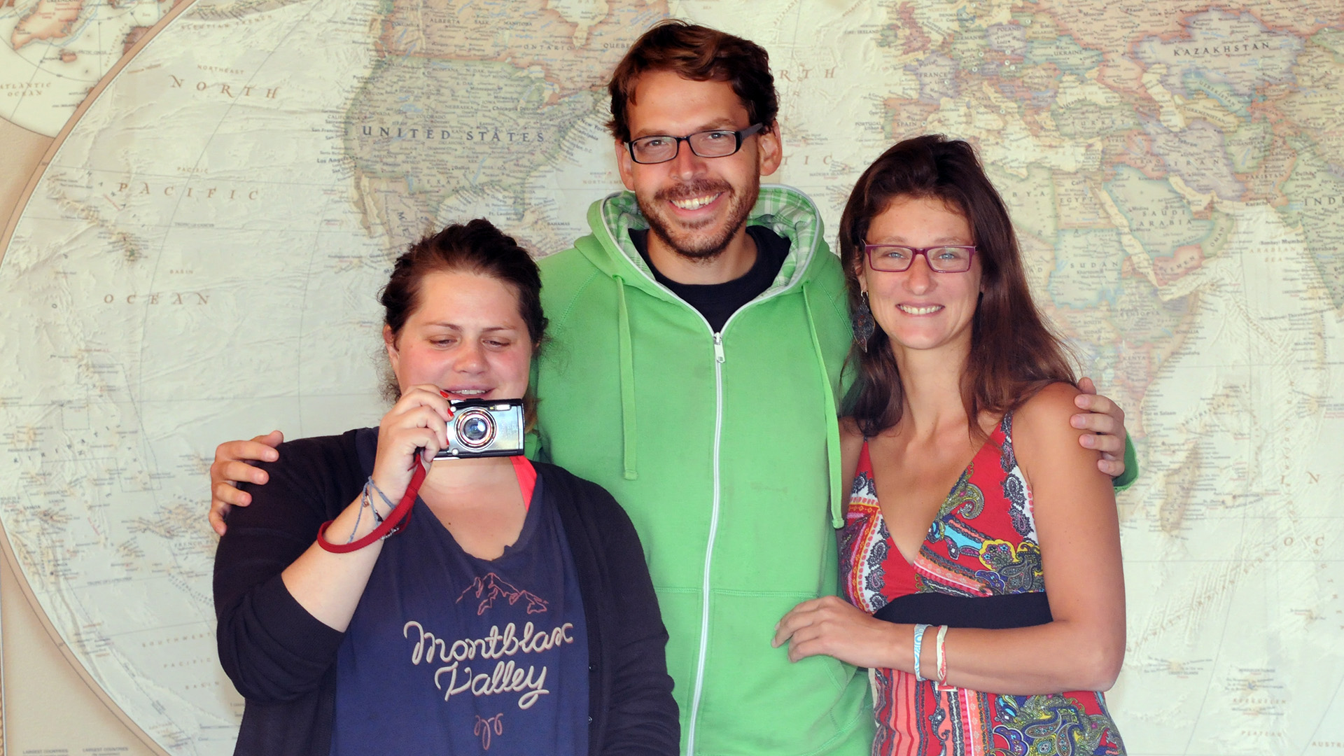three people standing in front of a world map