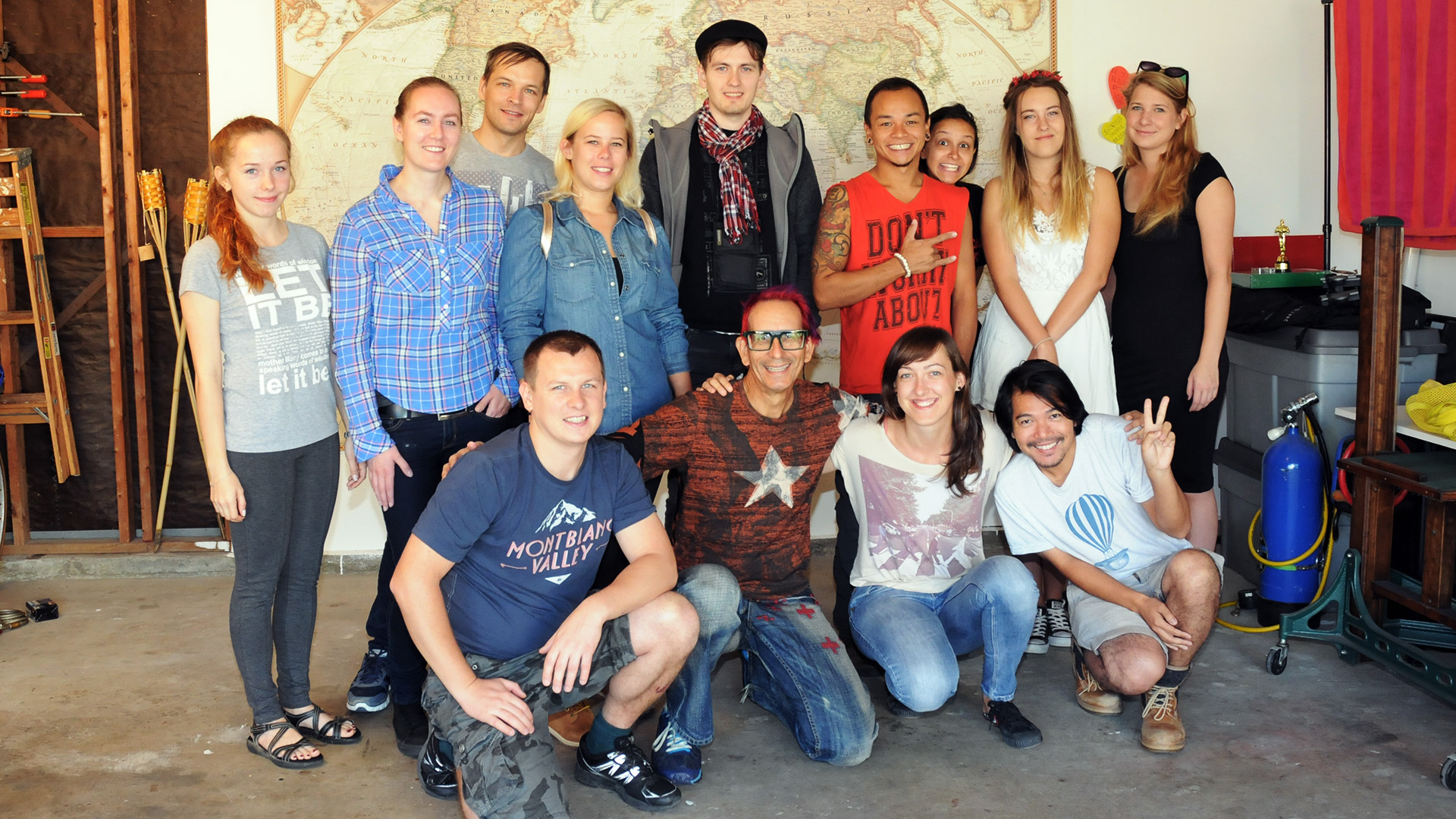 13 people posing for a group portrait in front of a large world map
