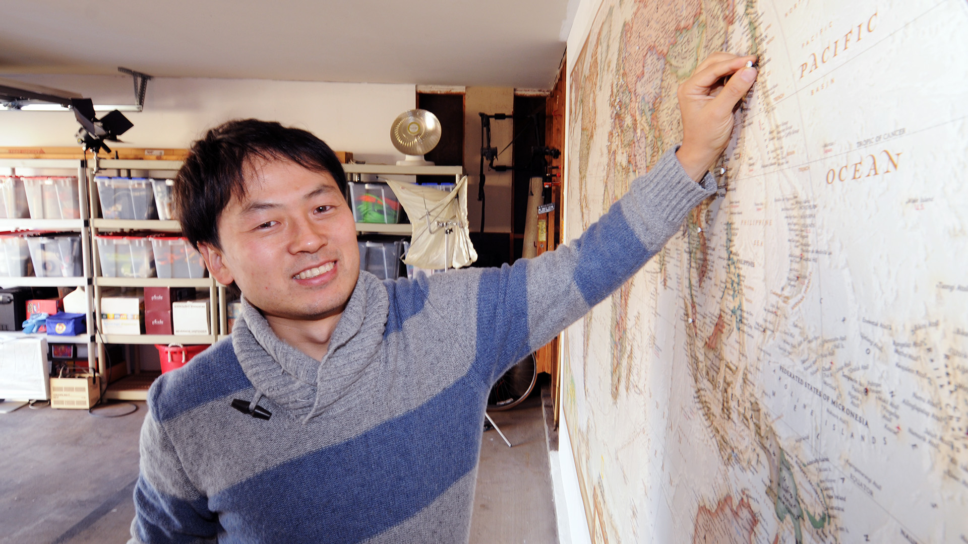 "photo of Tomo Ono pushing a ""Country #25"" pin into a world map. His pin is at Yokohama, Japan"
