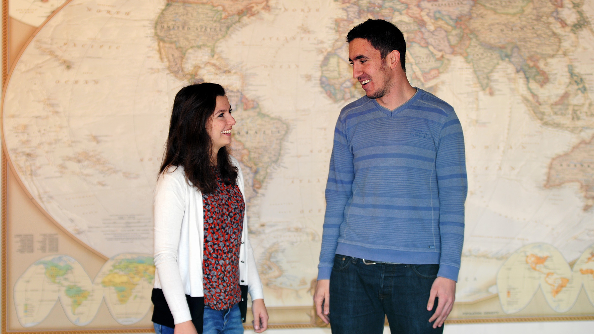 Rania and Moe stand in front of a world map and smile at each other