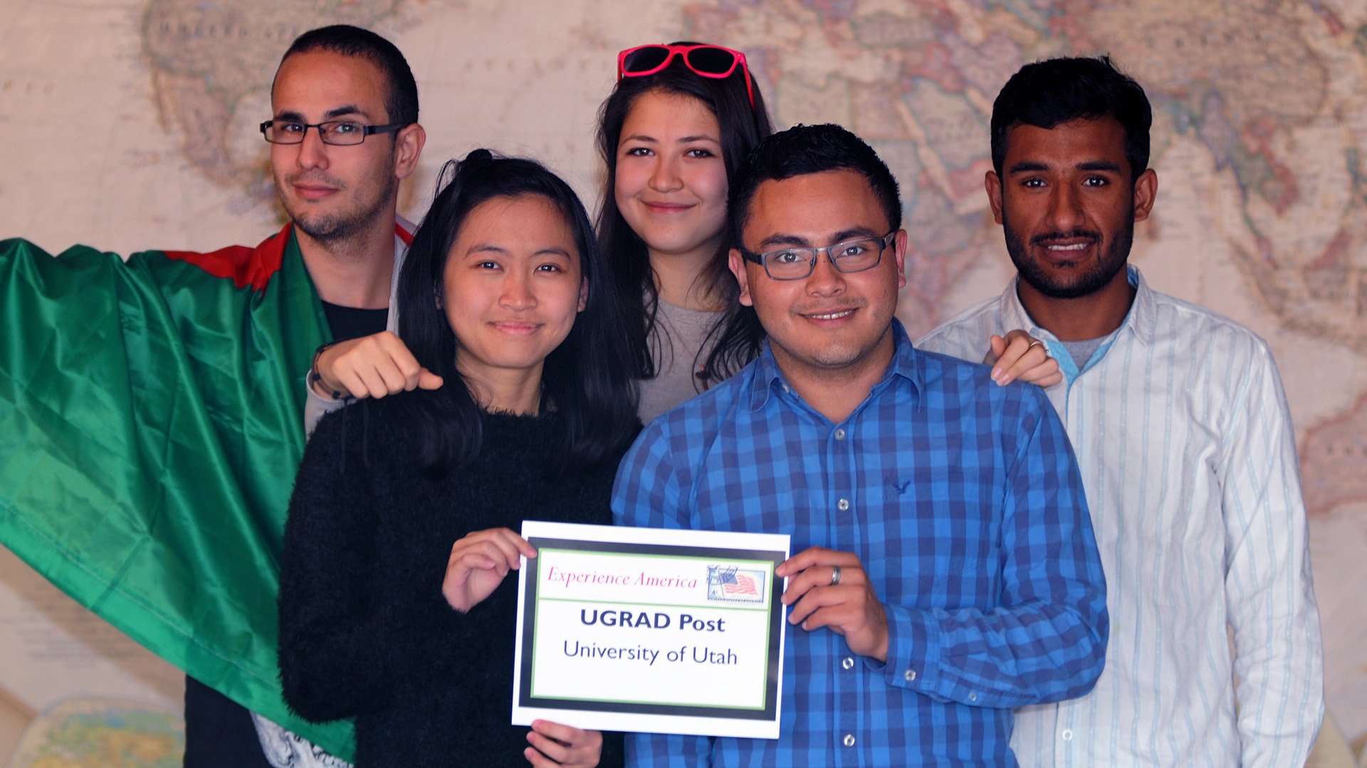 "Mehdi, Yin Chien, Aylar, Jimmy & Sagar standing in front of a large world map and holding a sign that reads ""Experience America, UGRAD Post, University of Utah"" Mehdi is wearing the Algerian flag."