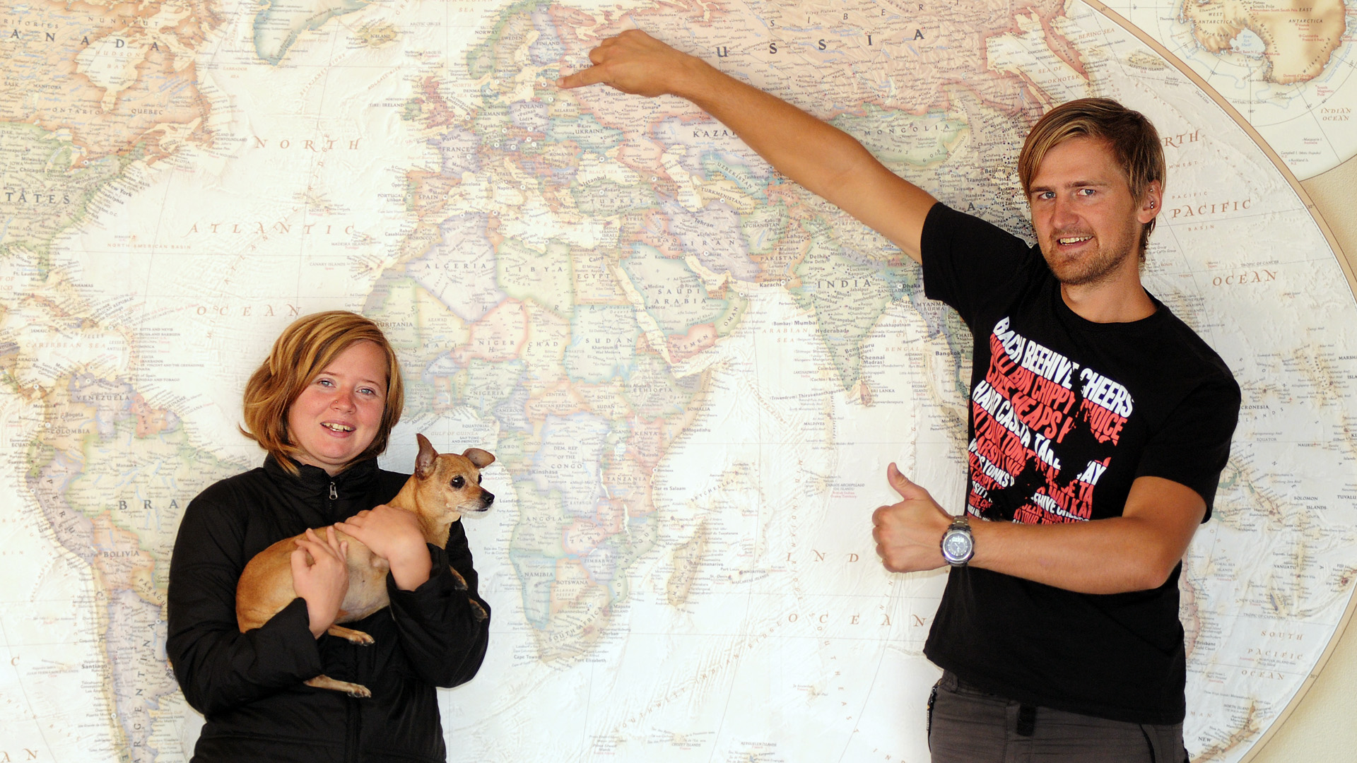 Vineta, Tiki & Krisjanis in front of a large world map. Vineta is holding Tiki and Krisjanis is pointing to Riga, Latvia on the world map