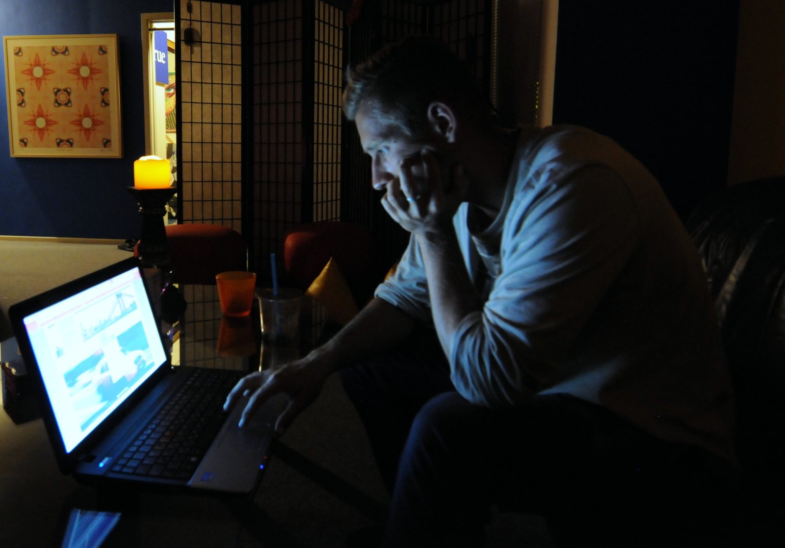 available light image of Denes, lit by his glowing laptop screen