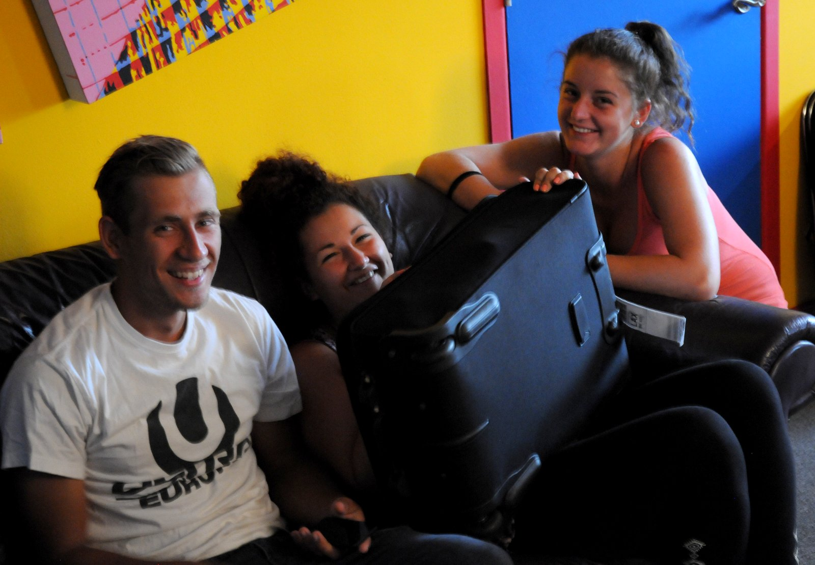 Denes, Csenge & Eszter sit on the purple couch in my living room. Csenge holds Denes suitcase on her lap and laughs