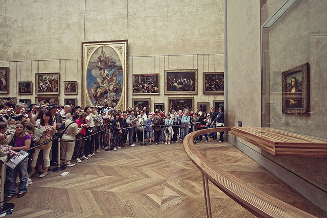 The crowd at the Mona Lisa  at The Louvre in Paris stands behind a huge wooden rail