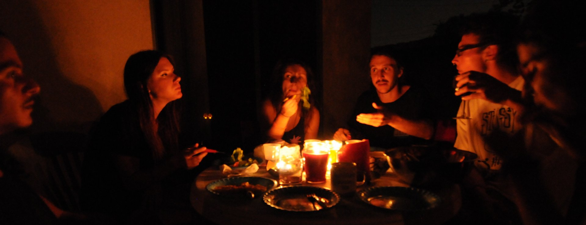 Night photo of people sitting around a candlelight table
