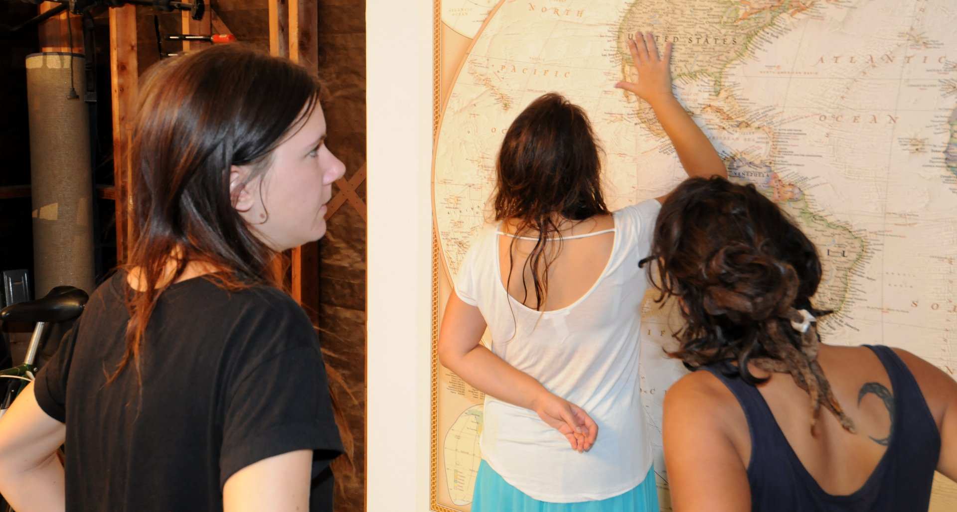 3 people looking at a 10 foot wide world map
