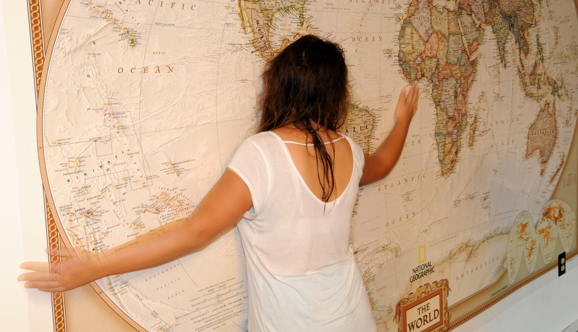 "Elena ""hugging"" a giant wall-sized map of the world"