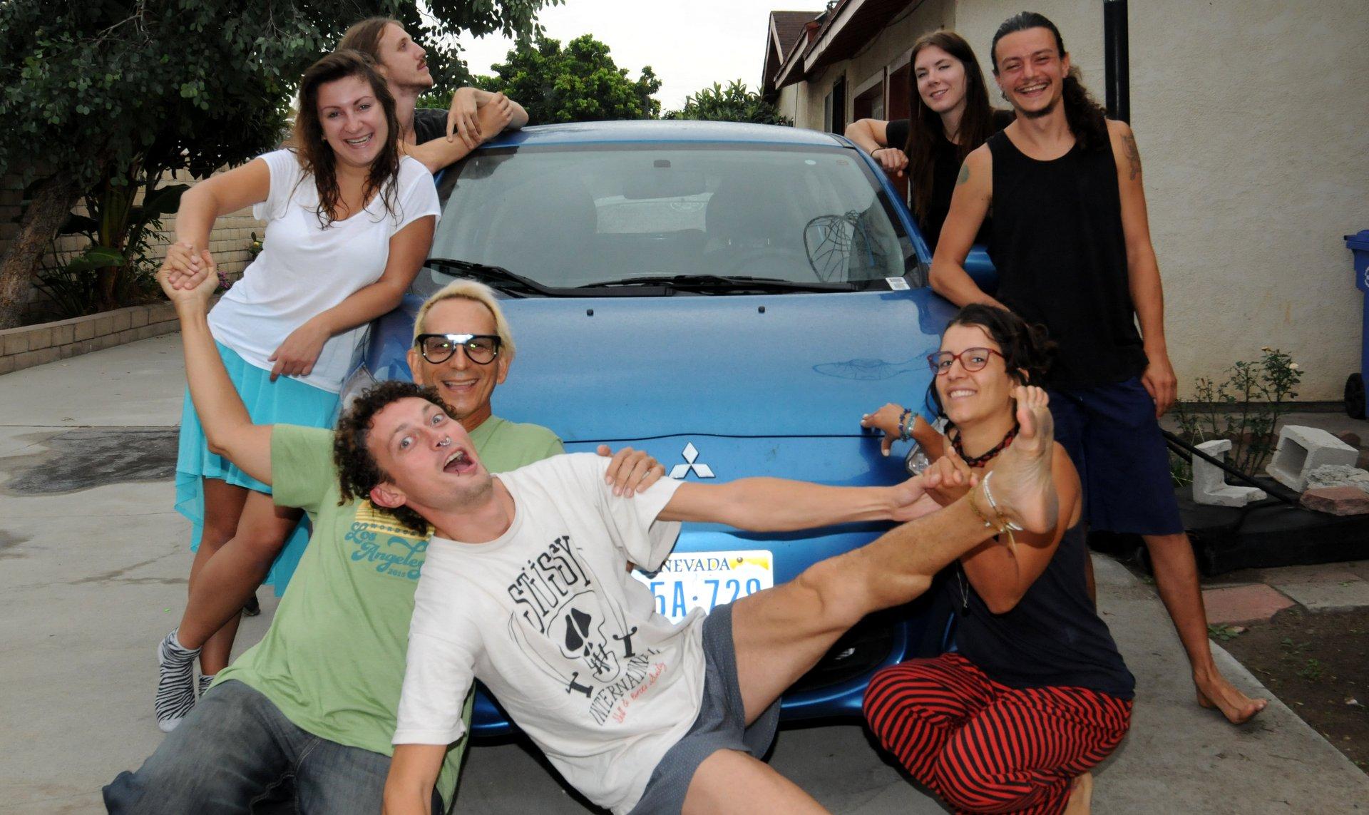 7 people posing around a car