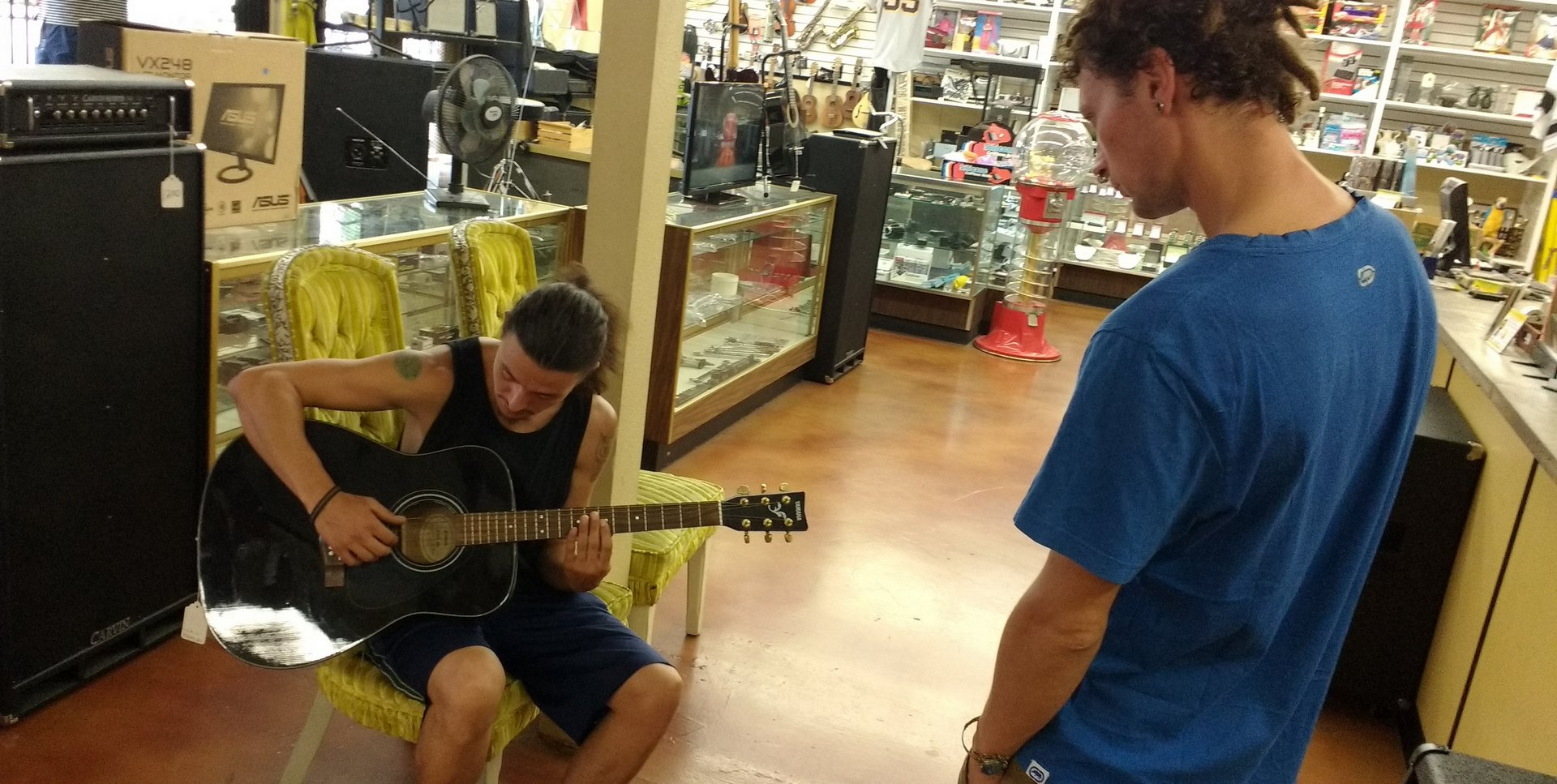 Antonio listening to Fabio try out guitars at the pawn shop