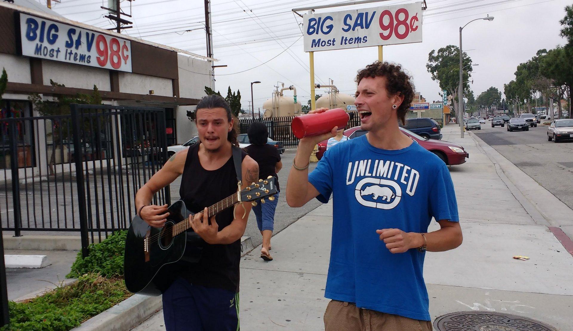Fabio & Antonio walking down the street singing and playing guitar