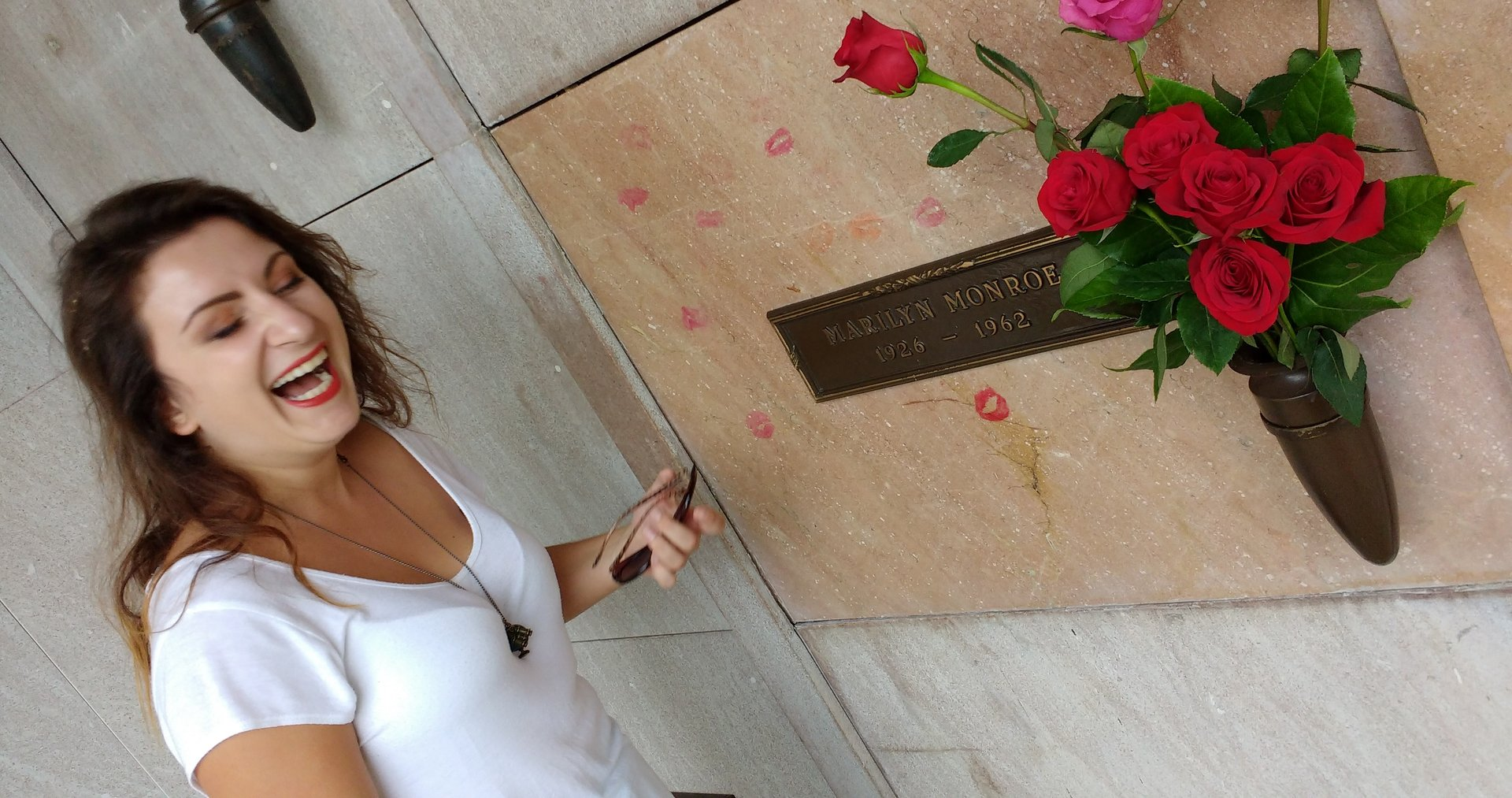 Elena at the grave site of Marilyn Monroe in Westwood, CA, smiling and applying lipstick to leave a lip print on the mausoleum wall