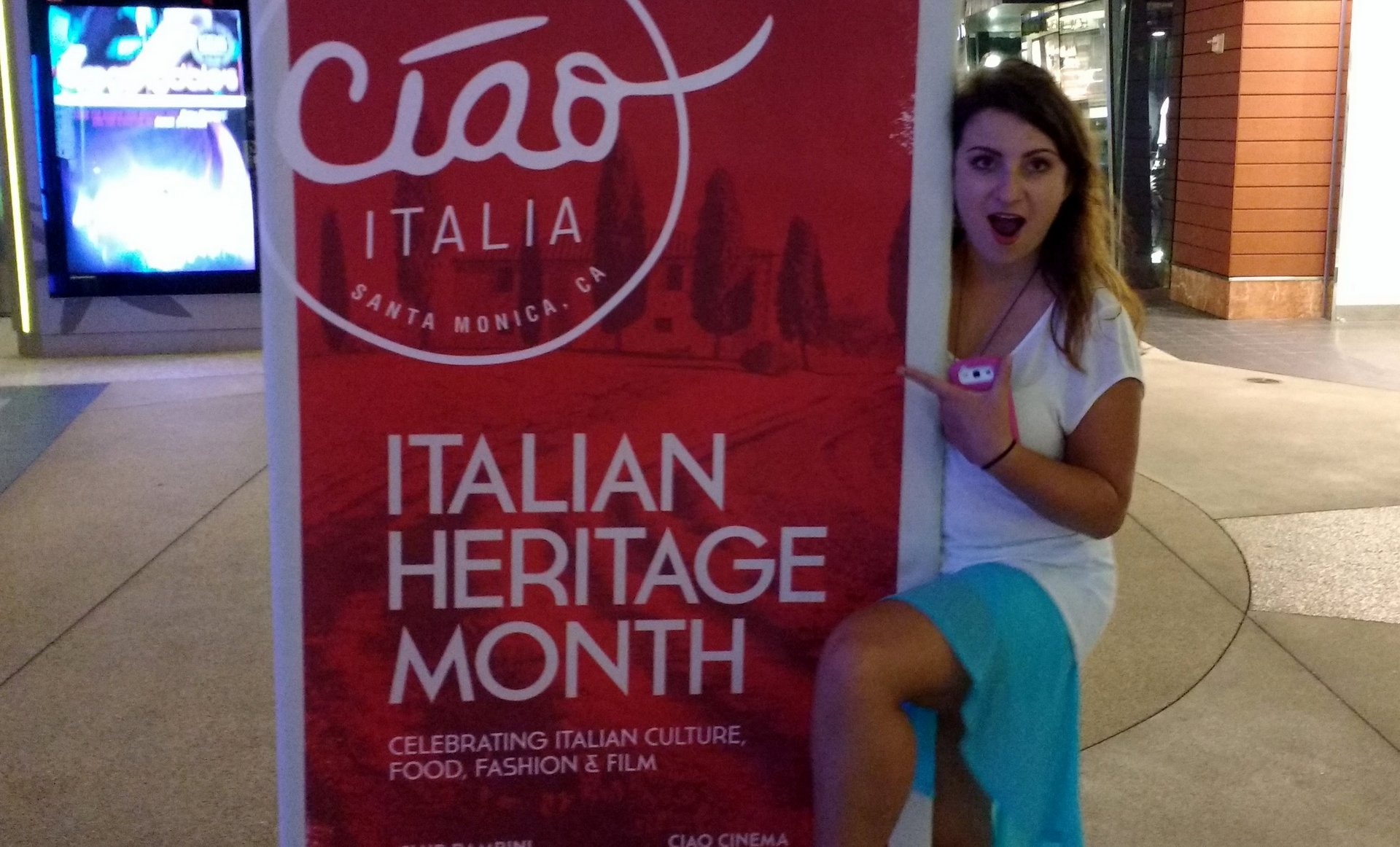 "Elena posing with a large banner that reads ""Italian Heritage Month"""