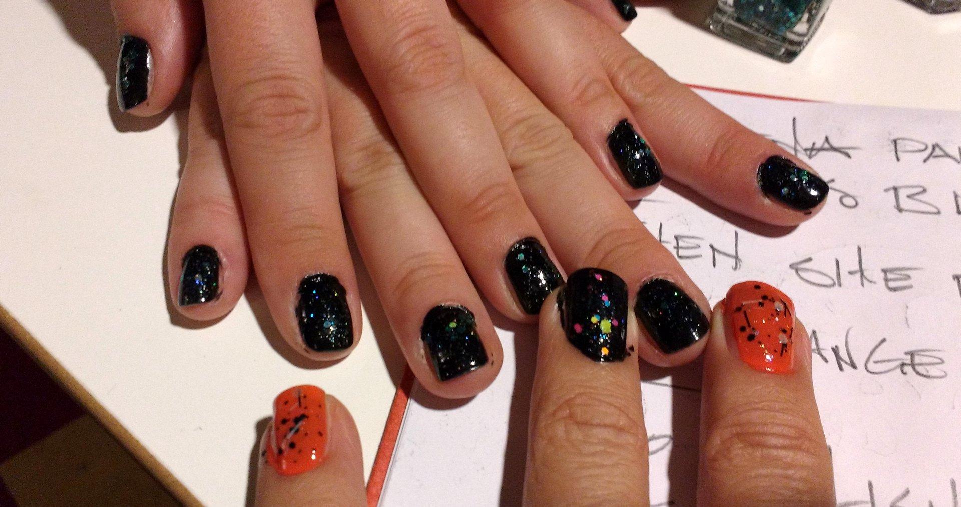 closeup of Elena & Glenn's hands with Orange and Black nail polish and glitter
