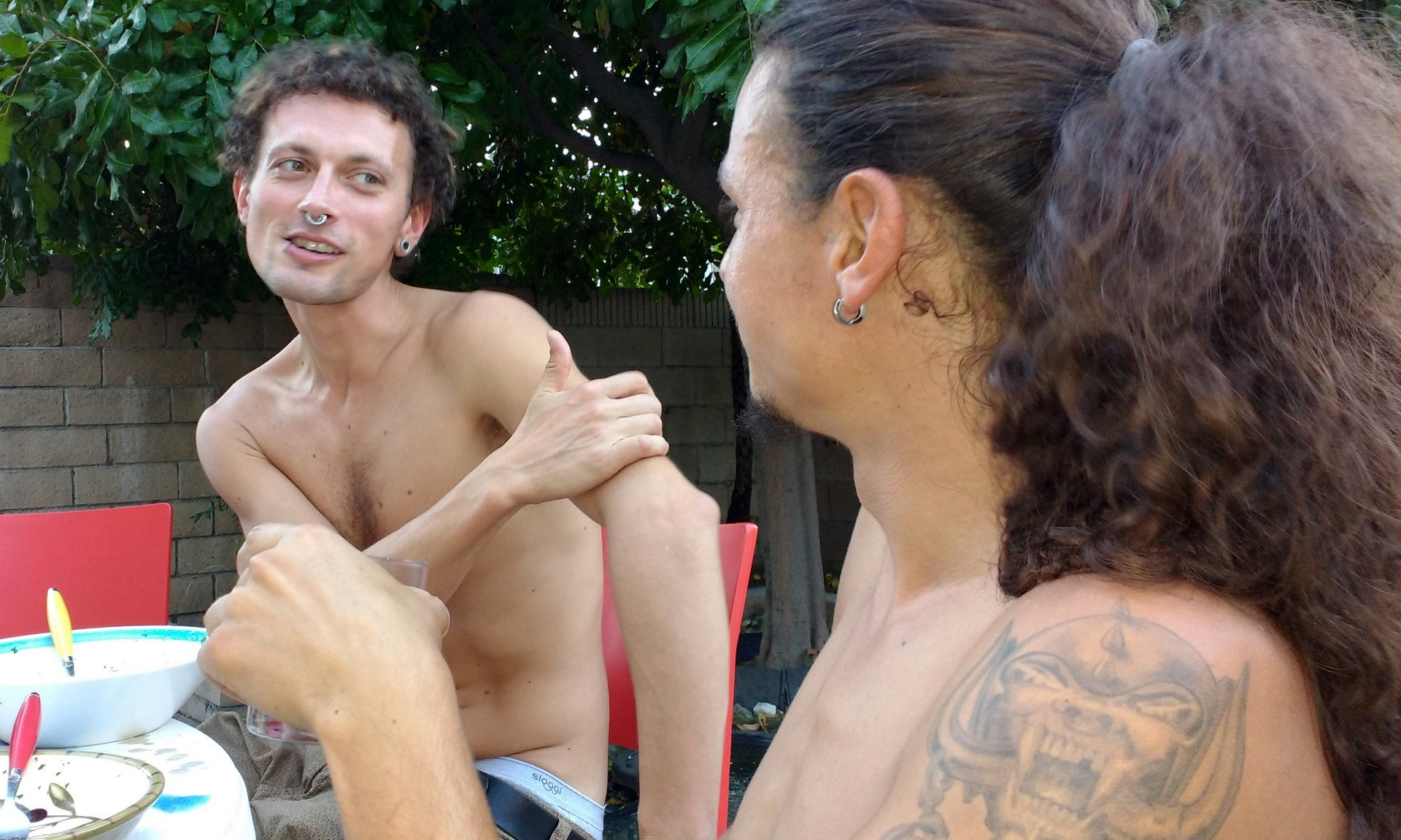 Two people, guys without shirts, sit at an outdoor table and eat a casual meal