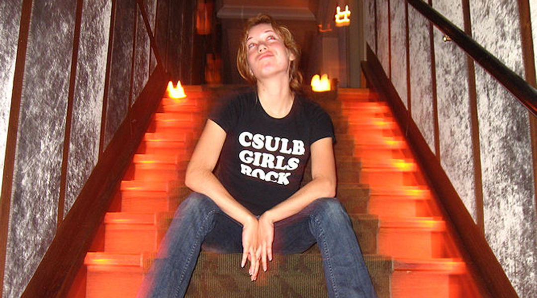 "Christine M. Johnson sitting in a dark stairwell and wearing a t-shirt that reads ""CSULB Girls Rock"""