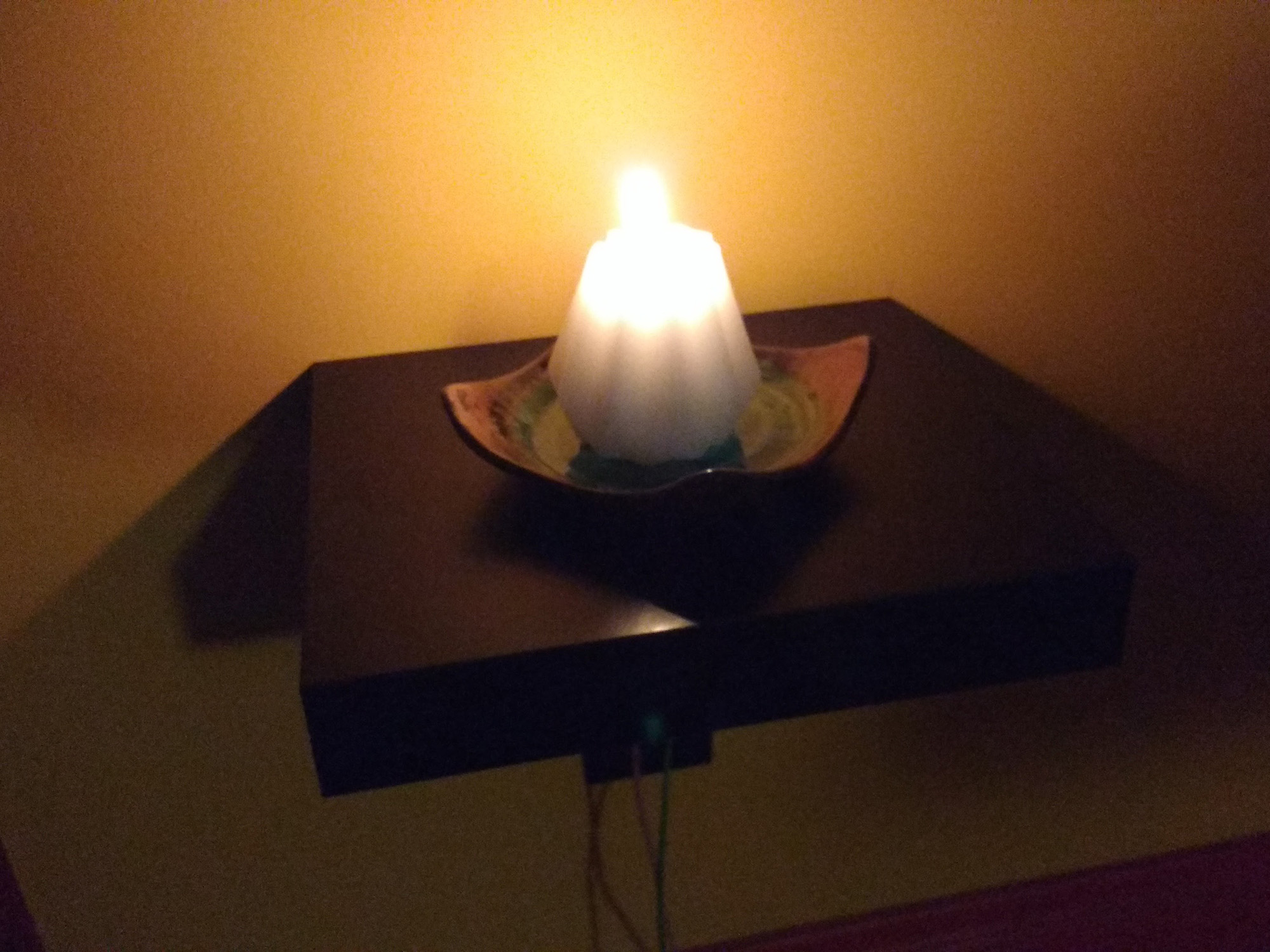 A candle and its flame glowing on a small shelf