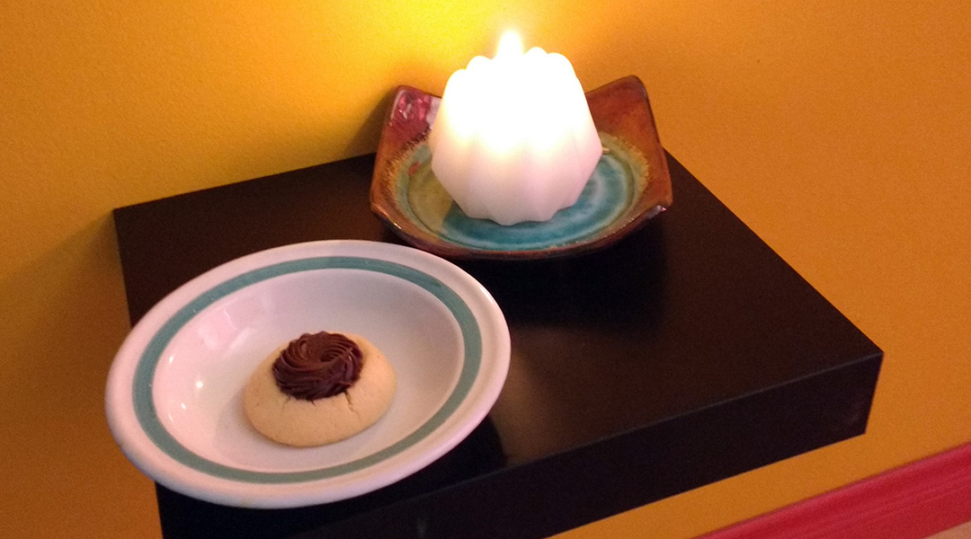 A candle and a cookie on a small shelf