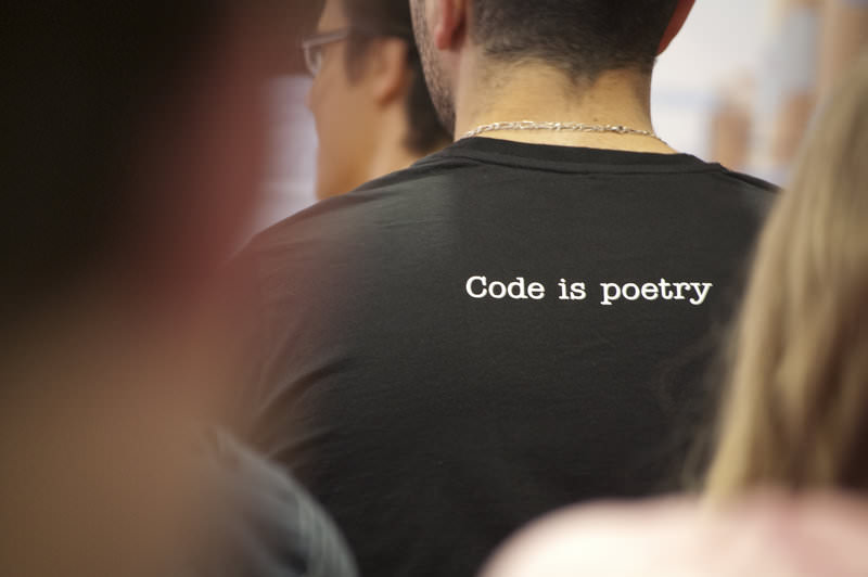 "photo of a guy in a ""Code is Poetry"" t-shirt"