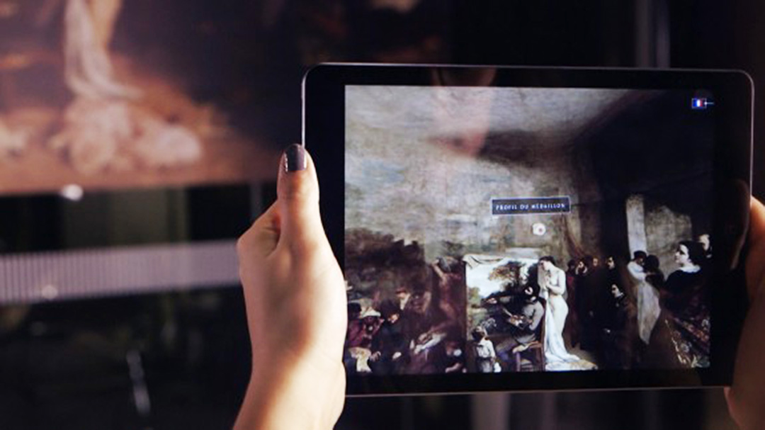 a hand holding an iPad in front of a painting by Courbet and showing interpretative materials on  the tablet screen