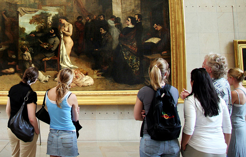 a group of people standing in the Musee d'Orsay looking at Gustave Courbet's painting The Painter's Studio