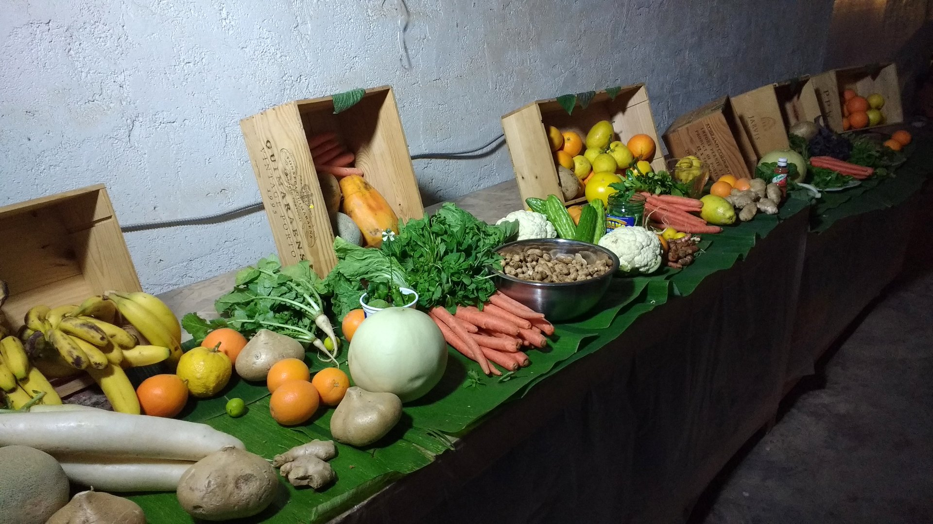 fruit & vegetables on a long wooden platform against a wall