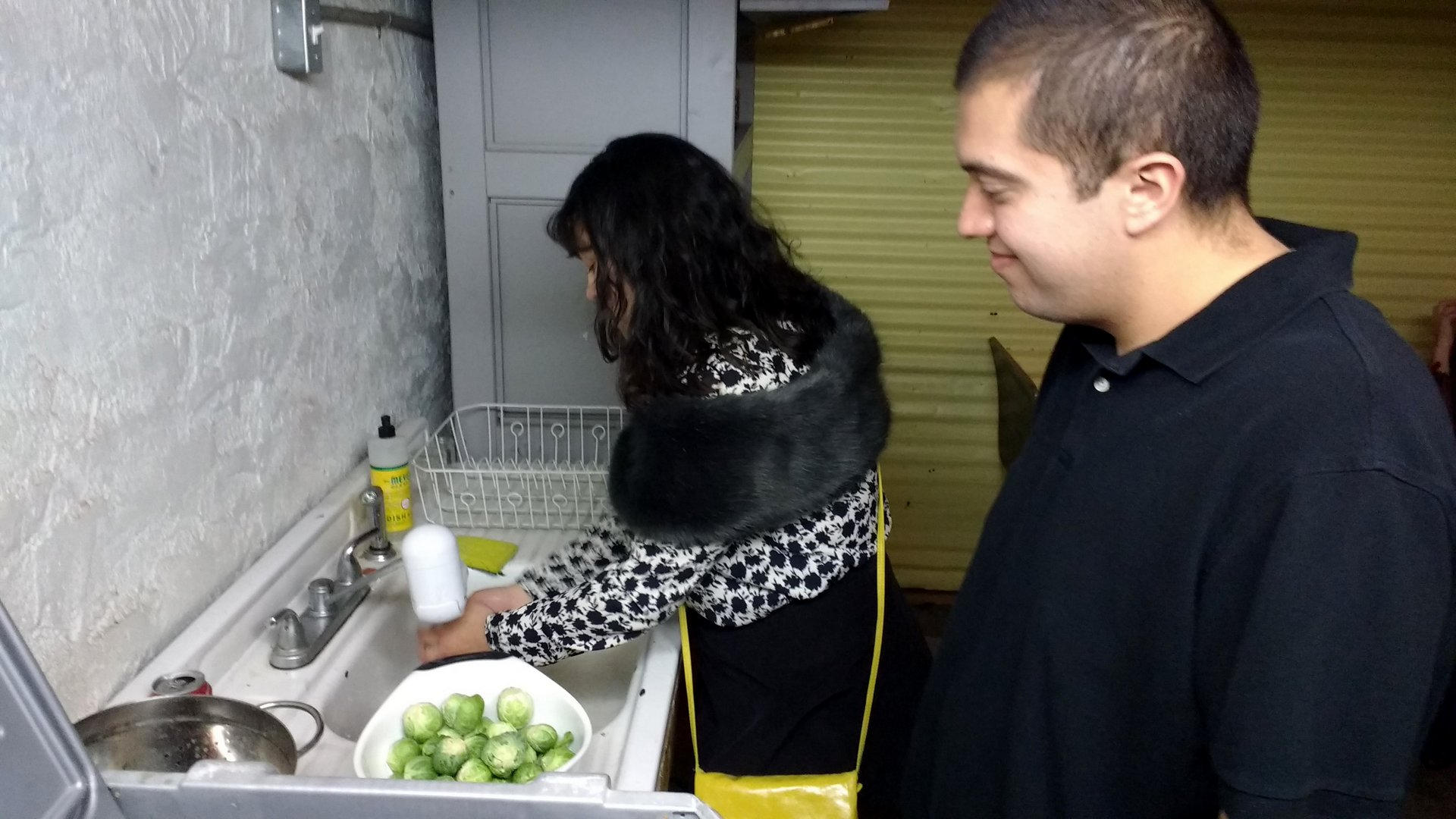 2 people washing Brussels sprouts at a sink