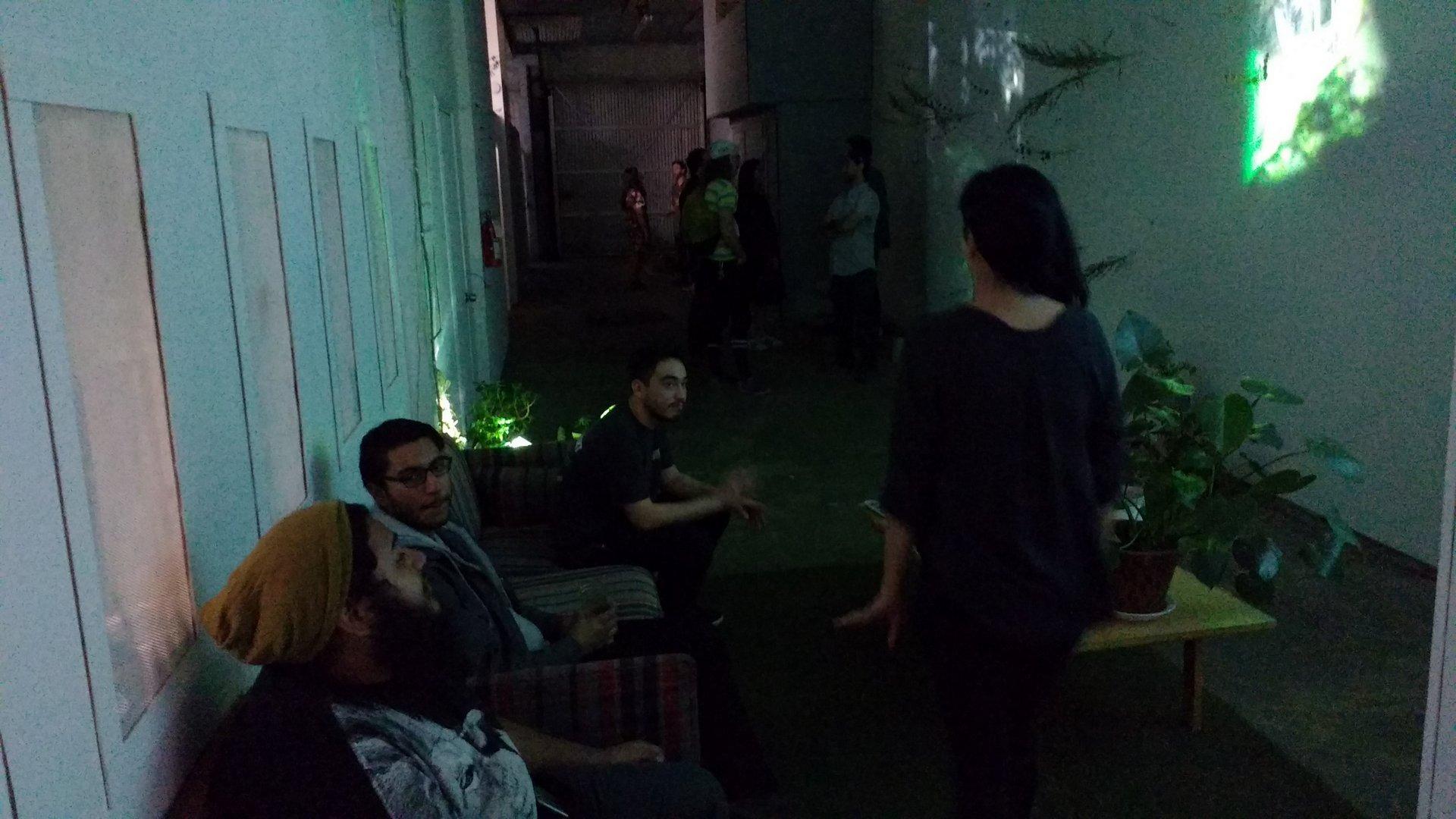 a long, dark hallway with various art installations