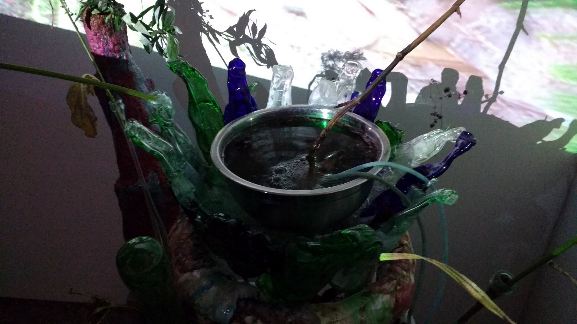 a bowl with bubbling liquid surrounded by slumped glass bottles