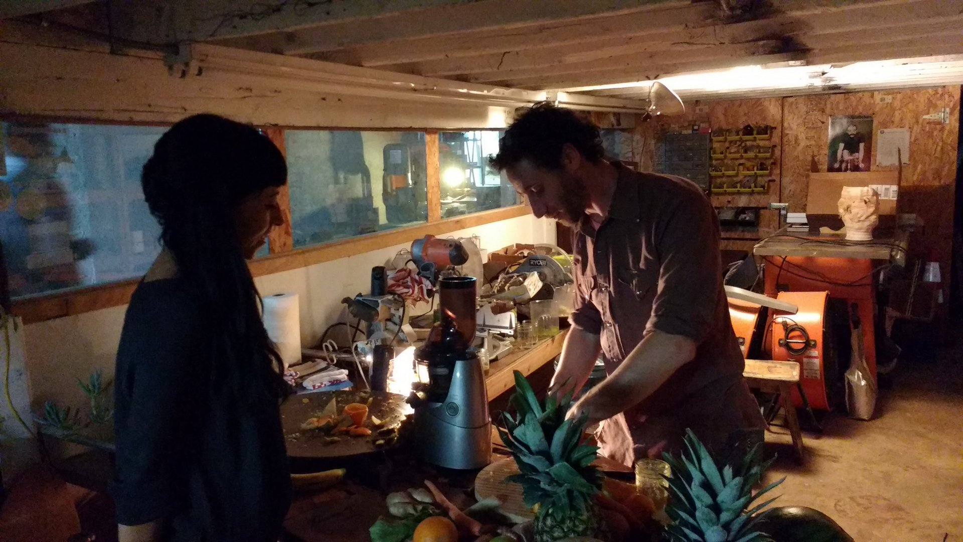 Maccabee Shelley making juice for, and sharing conversation with, an attendee at Dirtmaking