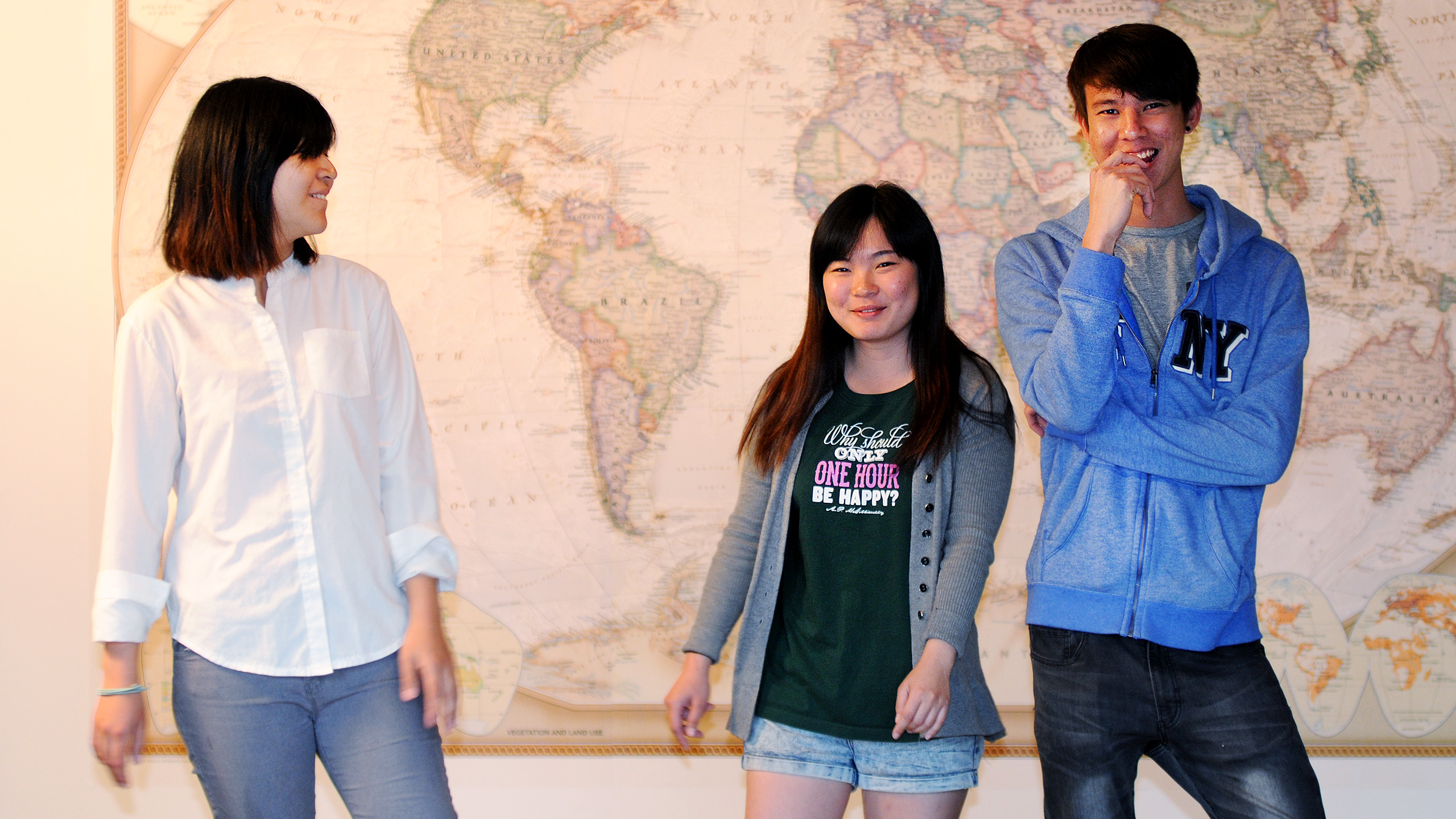 Ada, Joey & Kevin from Mayaysia standing in front of a large world map