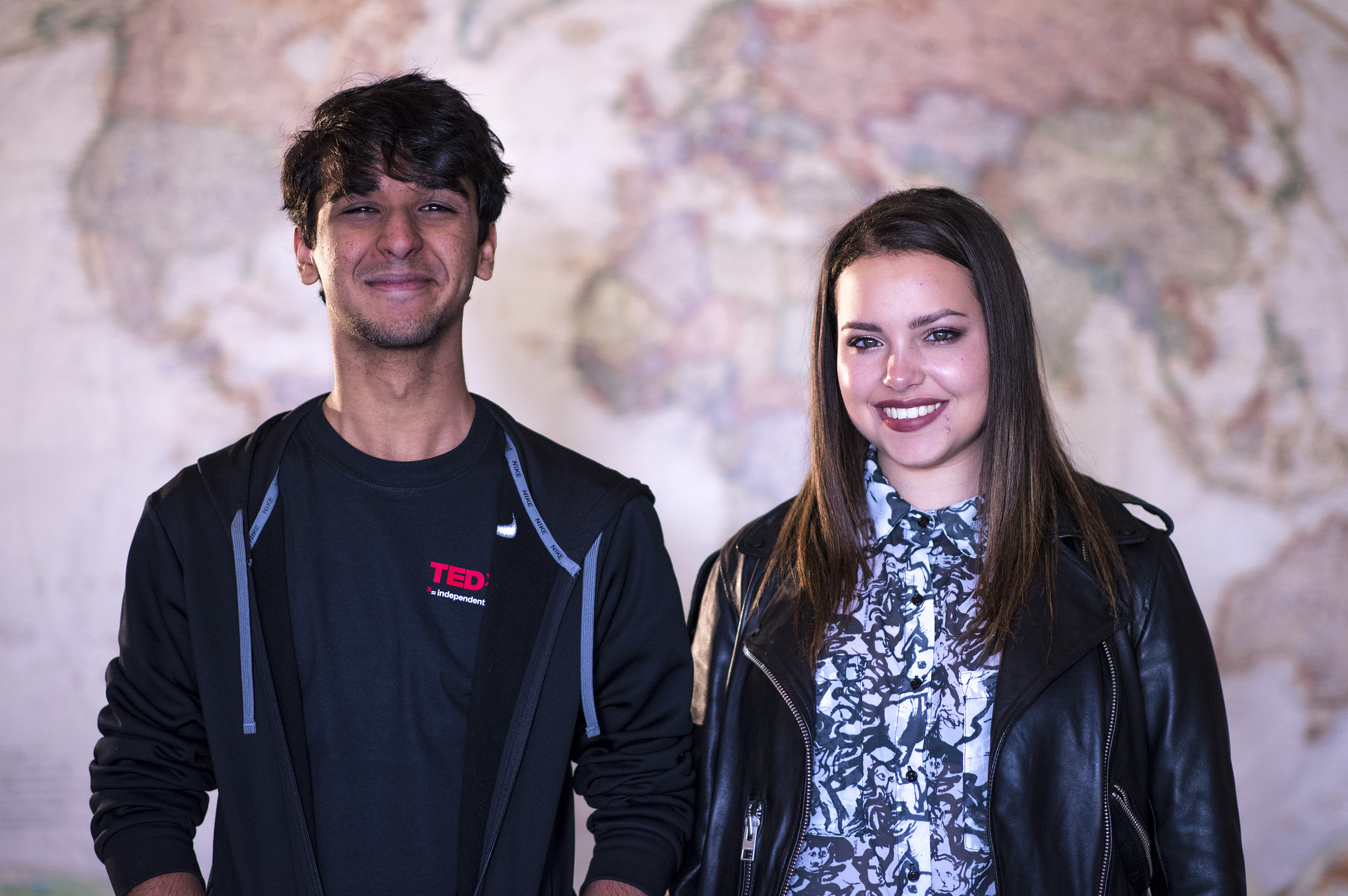 Mihir Kathpalia and Allison Bouganim dressed in black and standing in front of a large world map