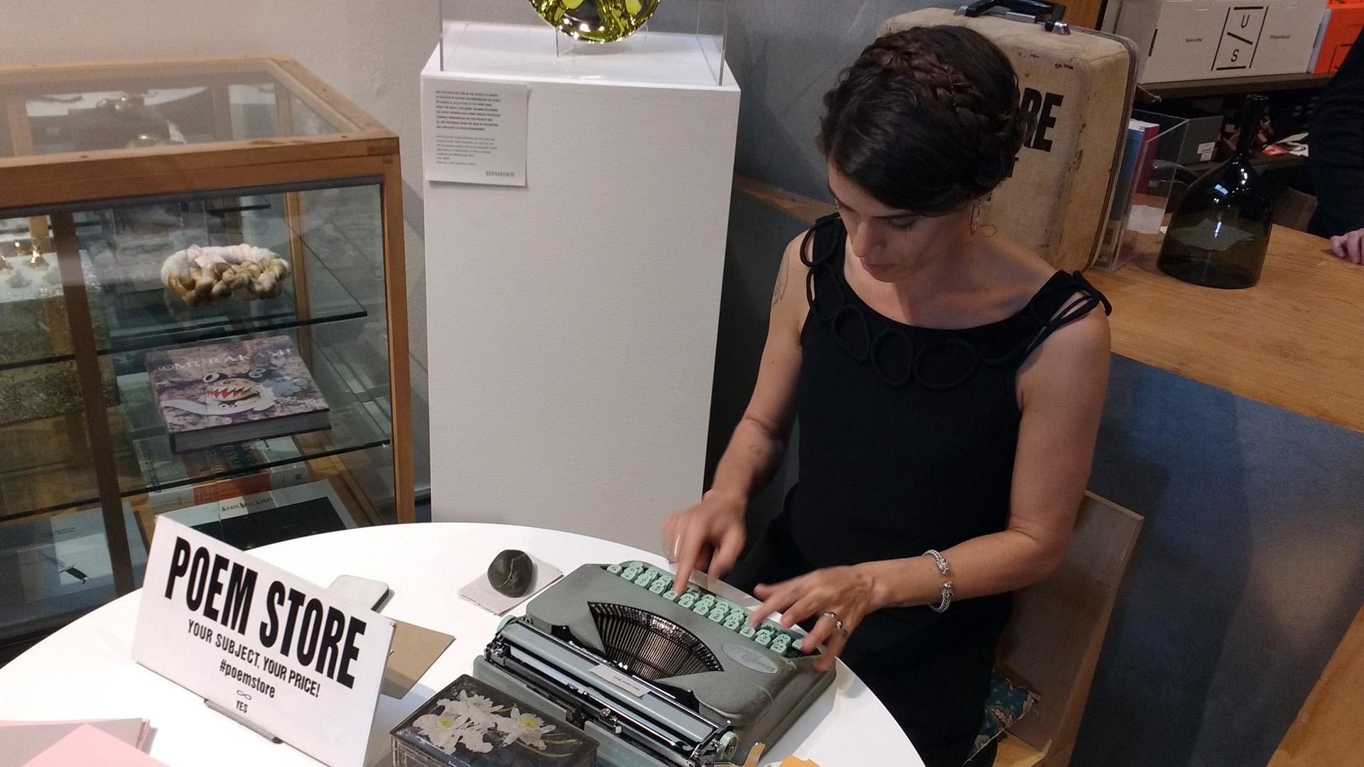 Jacqueline Suskin in the bookstore at The Geffen Contemporary at MOCA during the LA Art Book Fair. Suskin is typing a poem on a tiny piece of newsprint on an old, manual typewriter