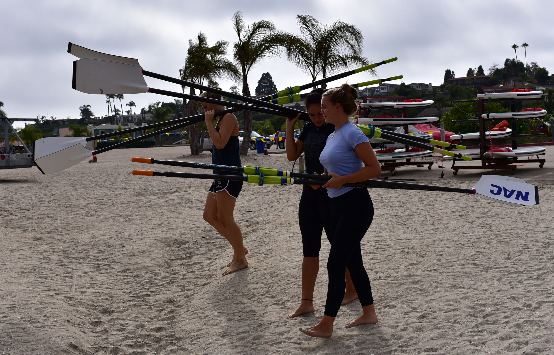 crew members carrying oars down to the water