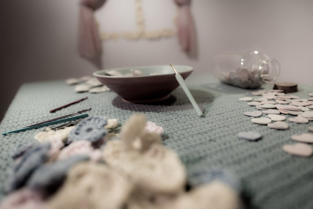 "Claudia Solorzano's abstract ""kitchen"" installation includes a window, an end table with a plant, an alphabet soup of ceramic letters in a corner, and here, in the center of the room, a table and chair, both covered in Solorzano's crochet work. On the table are a bowl of ceramic ravioli candy hearts, a bottle of smaller ceramic candy hearts, crocheting tools, and a pile of small crocheted hearts."