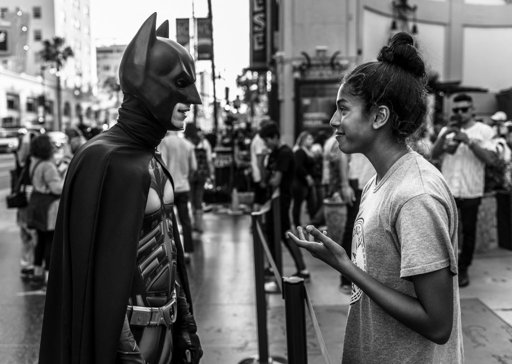 Nonfiction Photography (street photography) photo of a woman in conversation with Batman on the Hollywood Walk of Fame