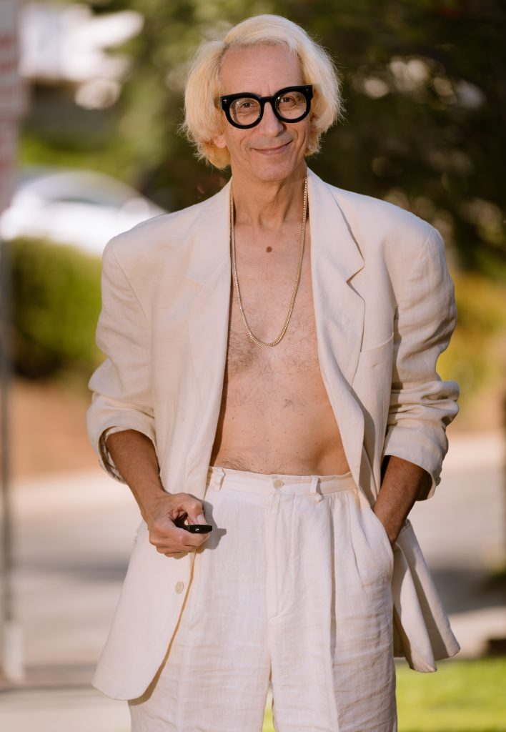 Glenn Zucman in a white, linen suit, mirroring a pose by Anne Hathaway for the cover of Shape Magazine.