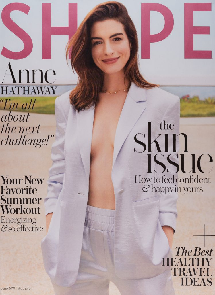 Anne Hathaway wearing a white jacket and pants.